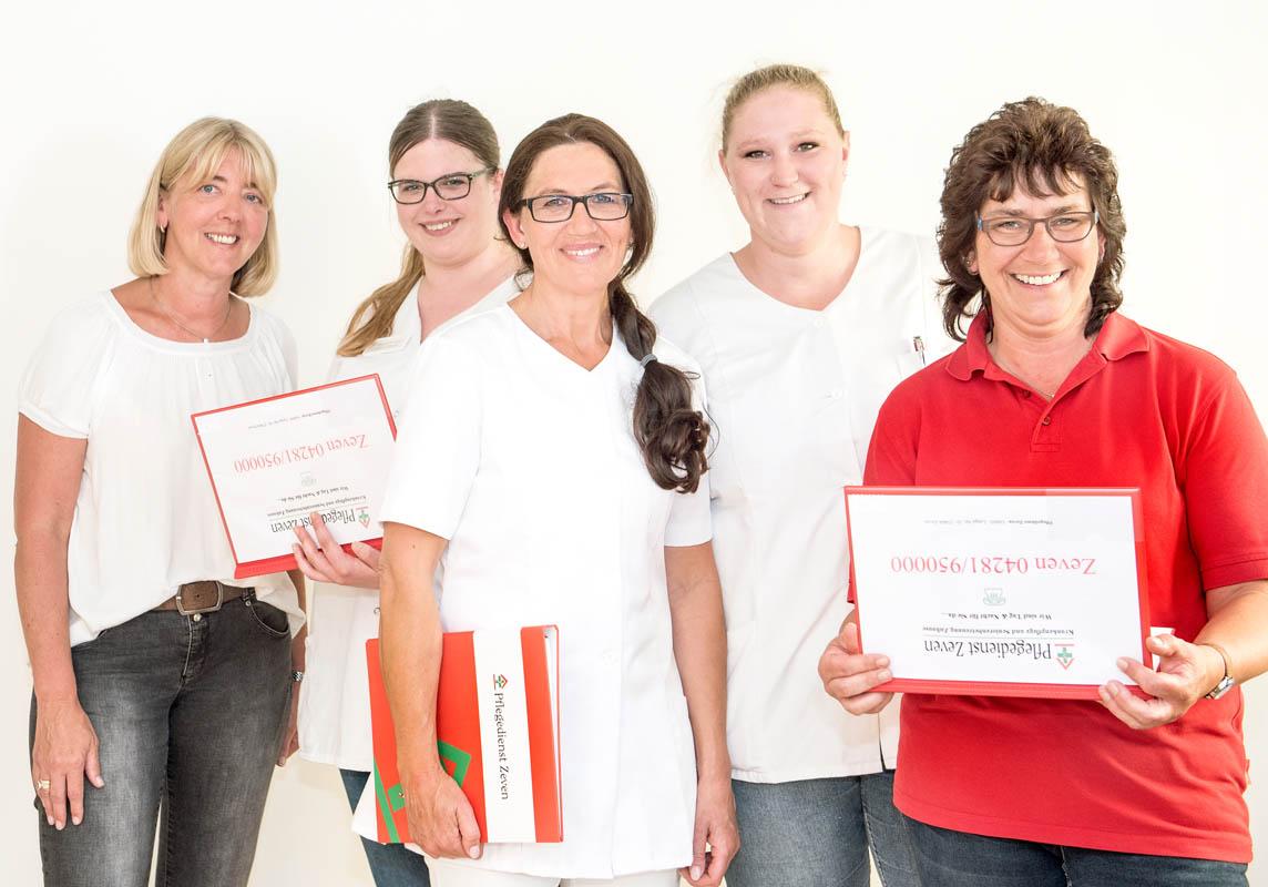 Pflegedienst Zeven Team halten rote Mappen in der Hand